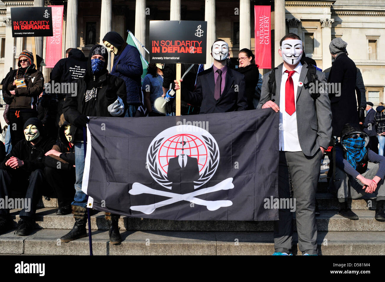 A group of protesters, some of them wearing anonymous masks at a rally in Trafalgar Square, London, UK. - Stock Image