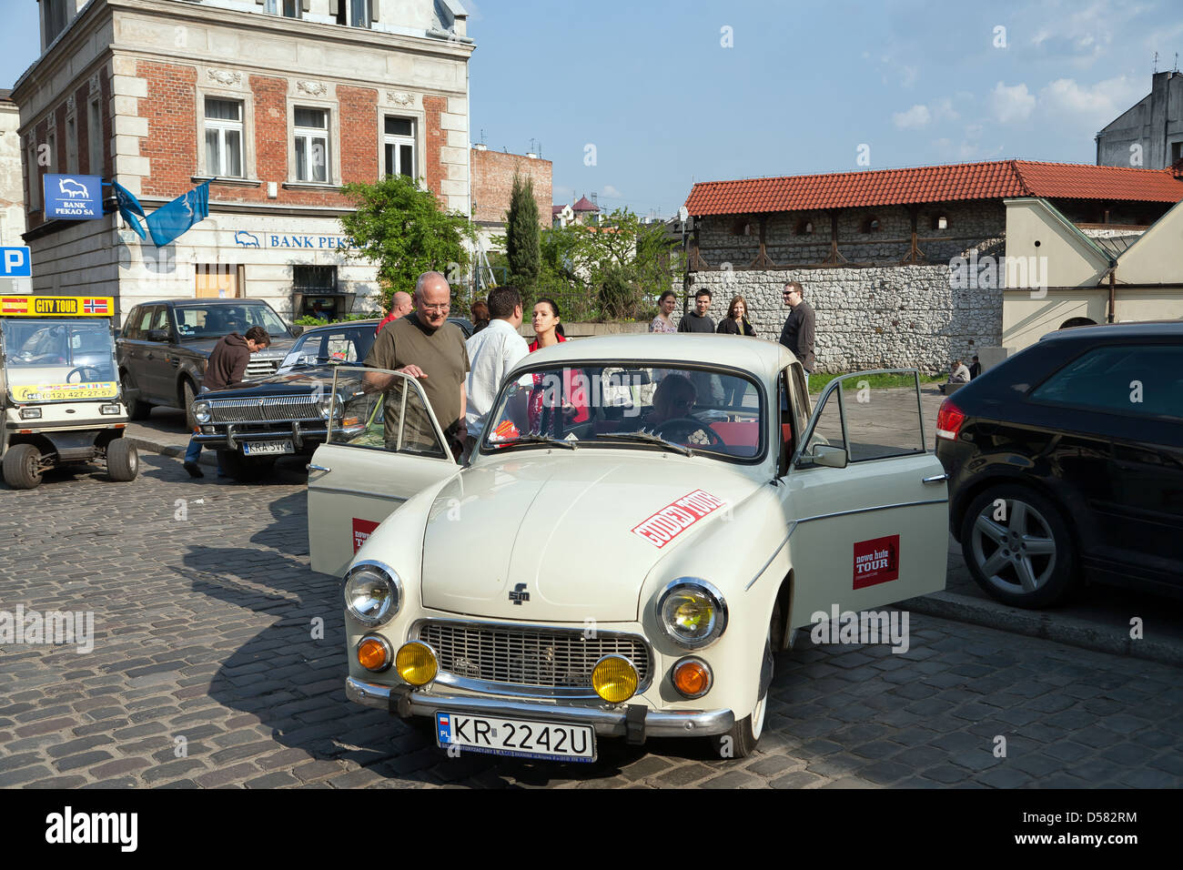 Krakow, Poland, Syrena 105 with tourists on Ulica Szeroka in Kazimierz - Stock Image