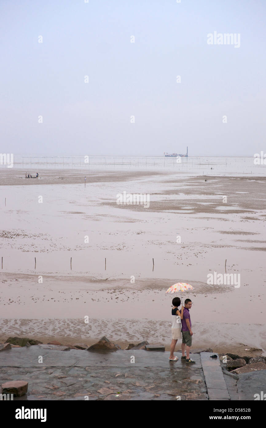 A girl holding an umbrella and boyfriend by South China Sea during low tide. - Stock Image