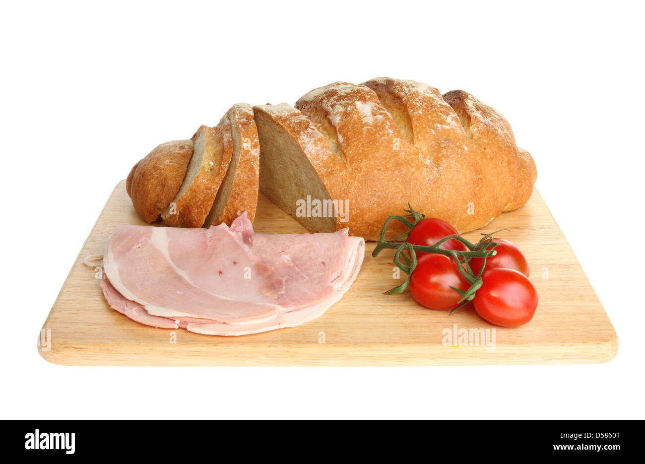 Freshly baked bloomer loaf with ham and tomatoes on a wooden board isolated against white - Stock Image