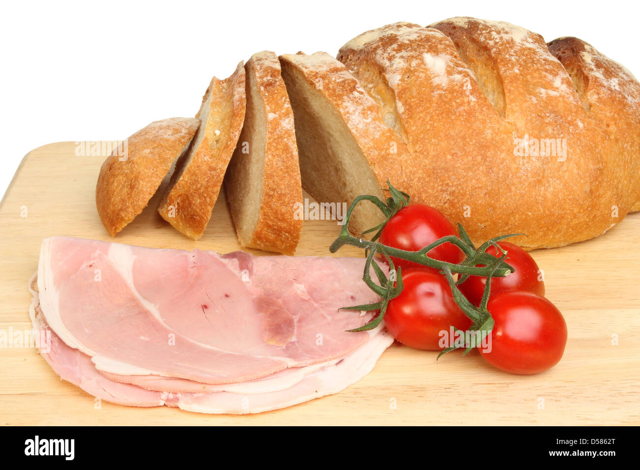 Freshly baked bloomer bread loaf with ham and tomatoes on a wooden board - Stock Image
