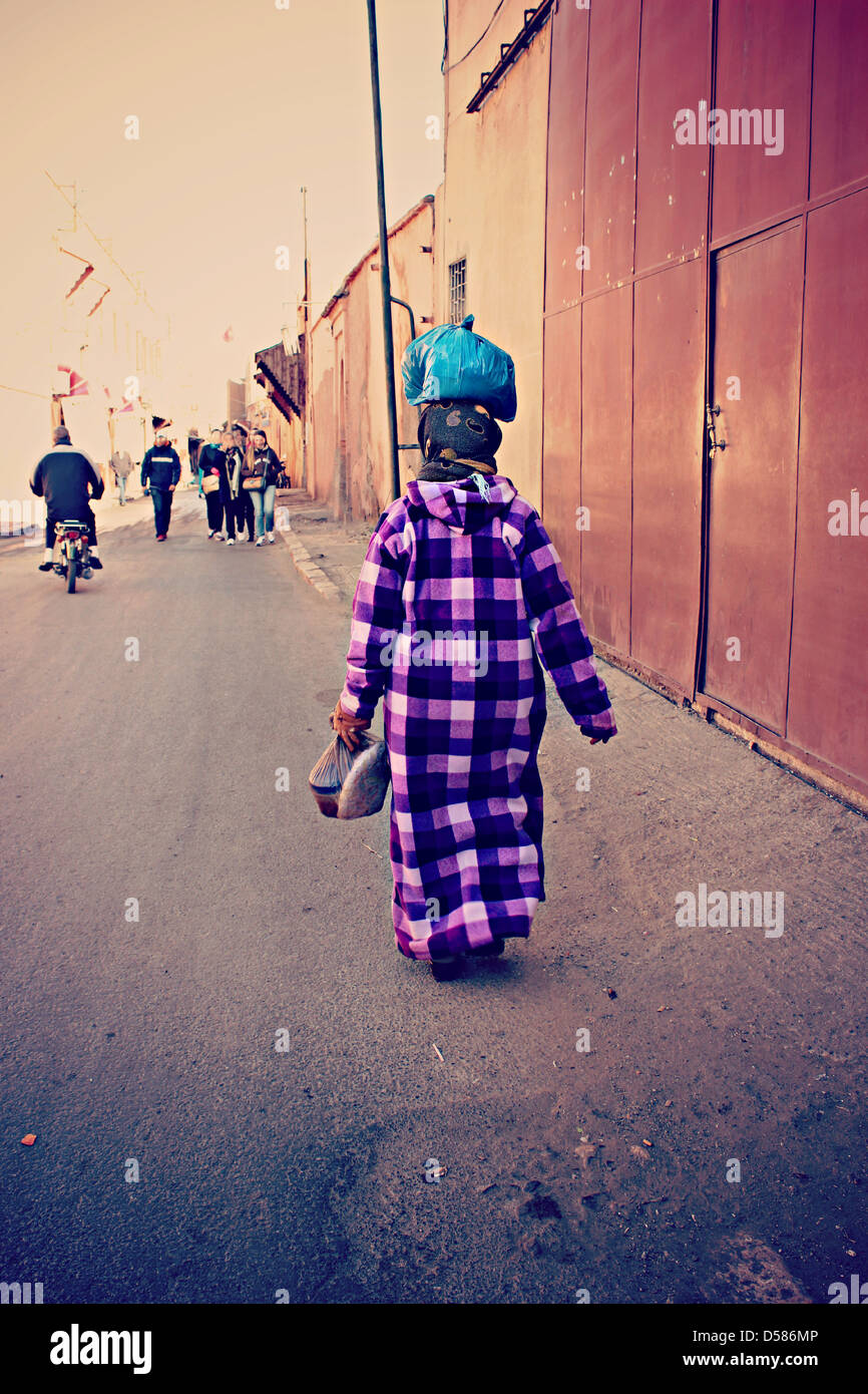 A lady walks the streets of Moroccan Almedina of Fez, with their colorful costumes, carrying your food! - Stock Image