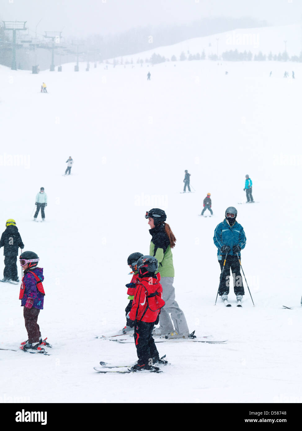 Children and adults skiing at Blue Mountain, Collingwood, Ontario, Canada alpine ski resort. - Stock Image
