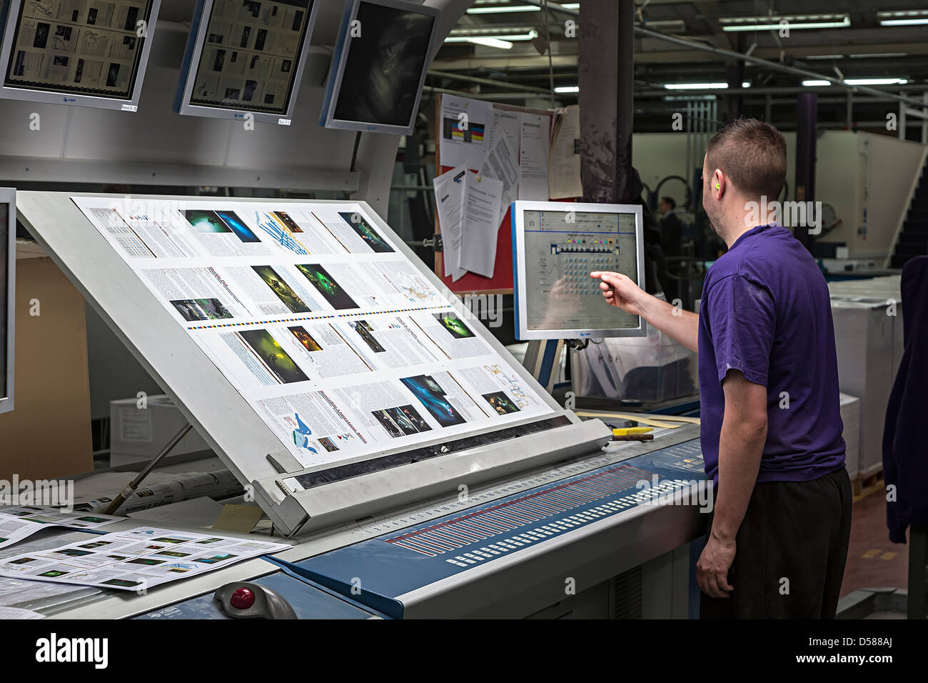 Assessing colour and adjusting offset litho printing press using computer touch screen UK - Stock Image