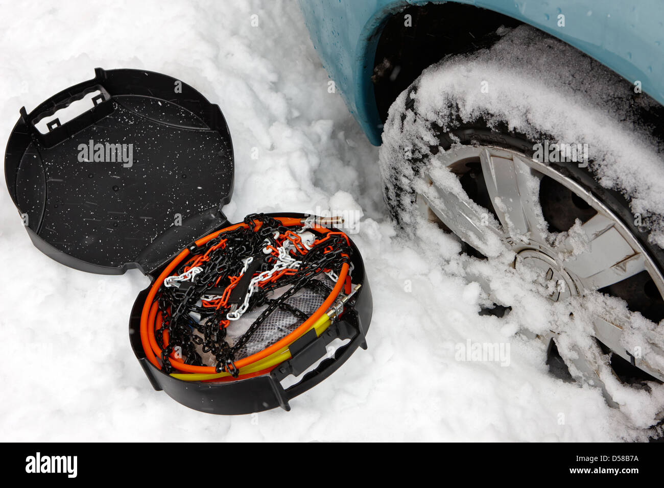 fitting snowchains to car in heavy winter snowstorm newtownabbey uk - Stock Image