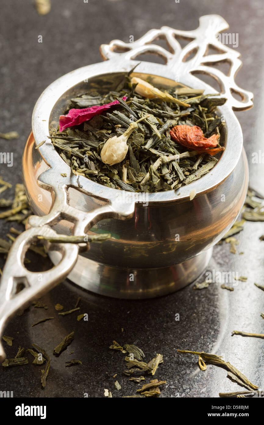 Tea strainer with jasmine and rose green tea - Stock Image