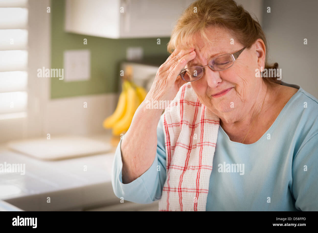 Sad Crying Senior Adult Woman At Kitchen Sink in Home. - Stock Image