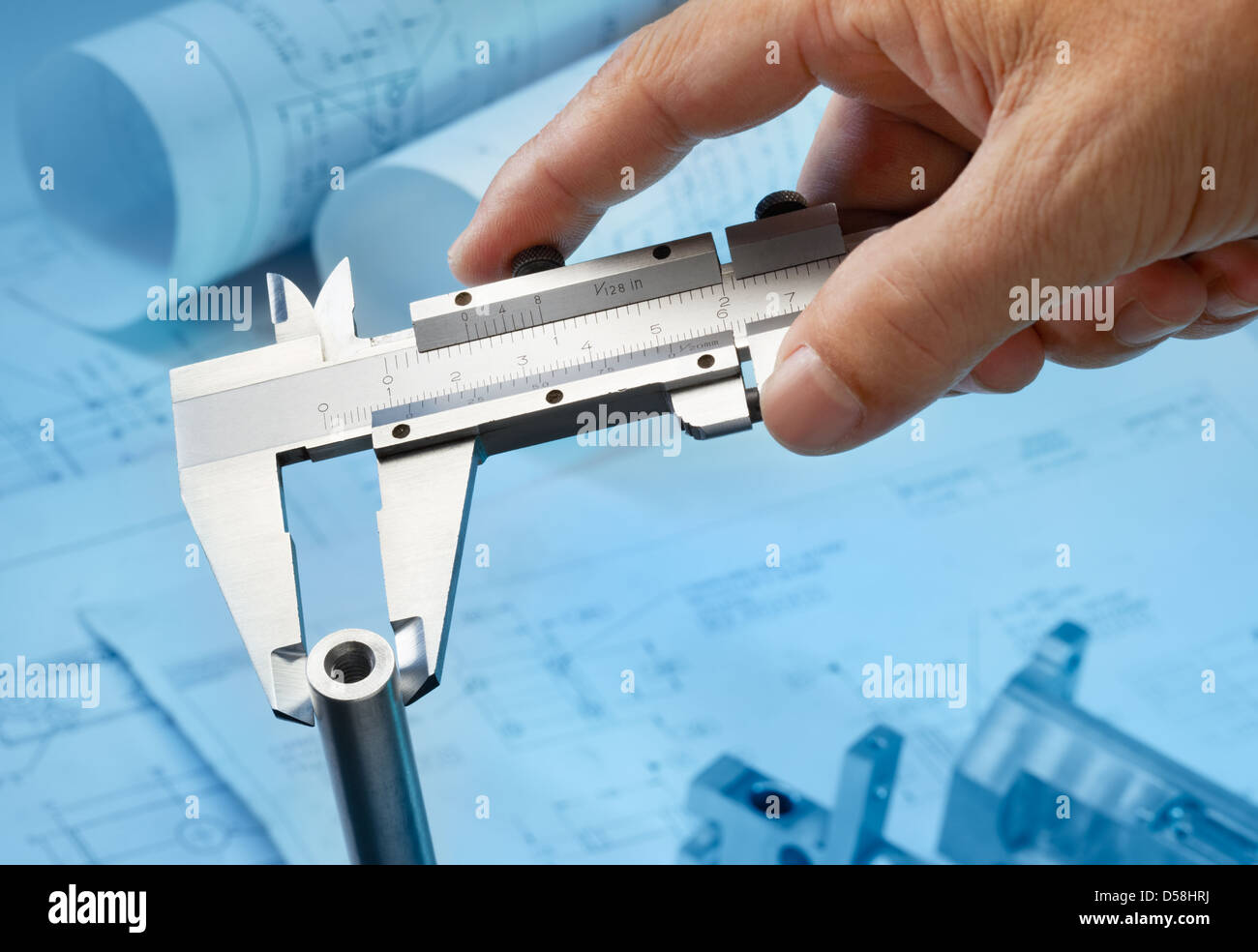 measuring machine part with caliper, blueprint as background - Stock Image