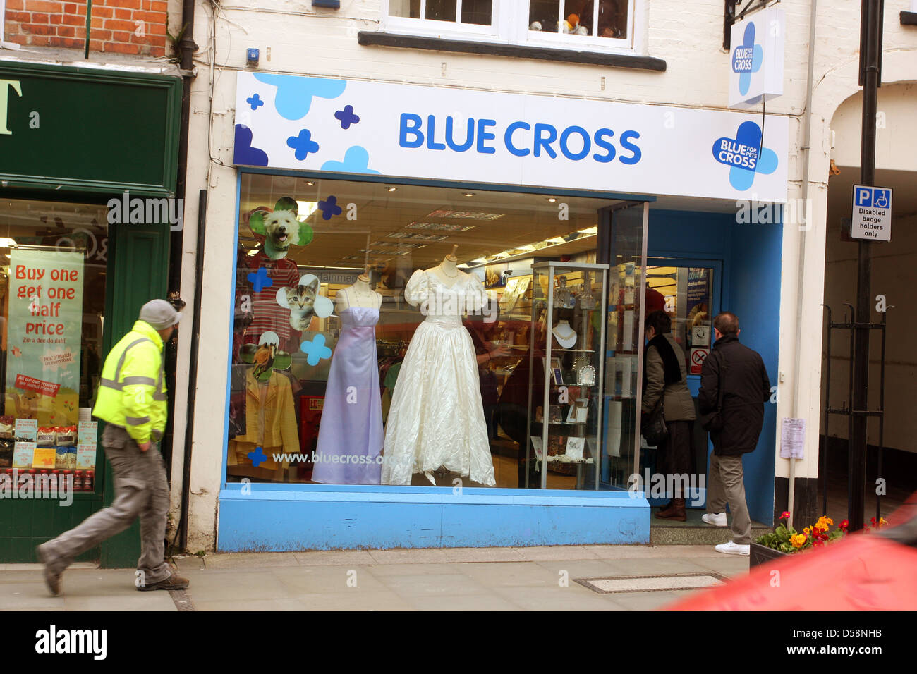 Customers entering the Blue cross animal charity shop on the high street in Wells, Somerset, March 2013 - Stock Image
