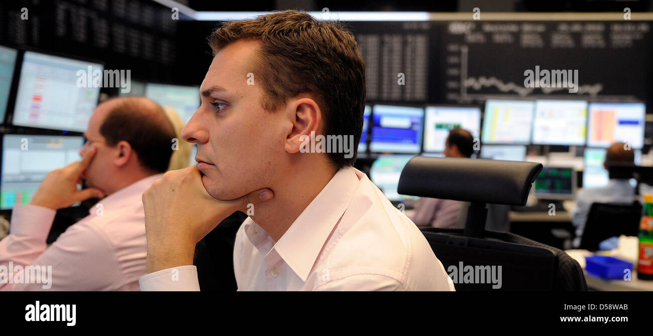 A jobber looks thoughtful on his computer screens at stock exchange in Frankfurt/Main, Germany, 25 May 2010. Burdened - Stock Image
