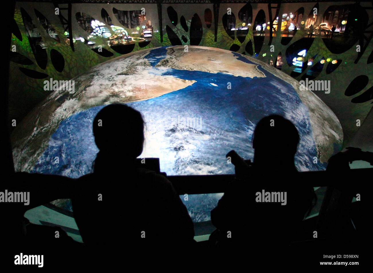 Visitors of the central Theme Pavilion 'Urban Planet' follow a multivision show about growth and decay of - Stock Image