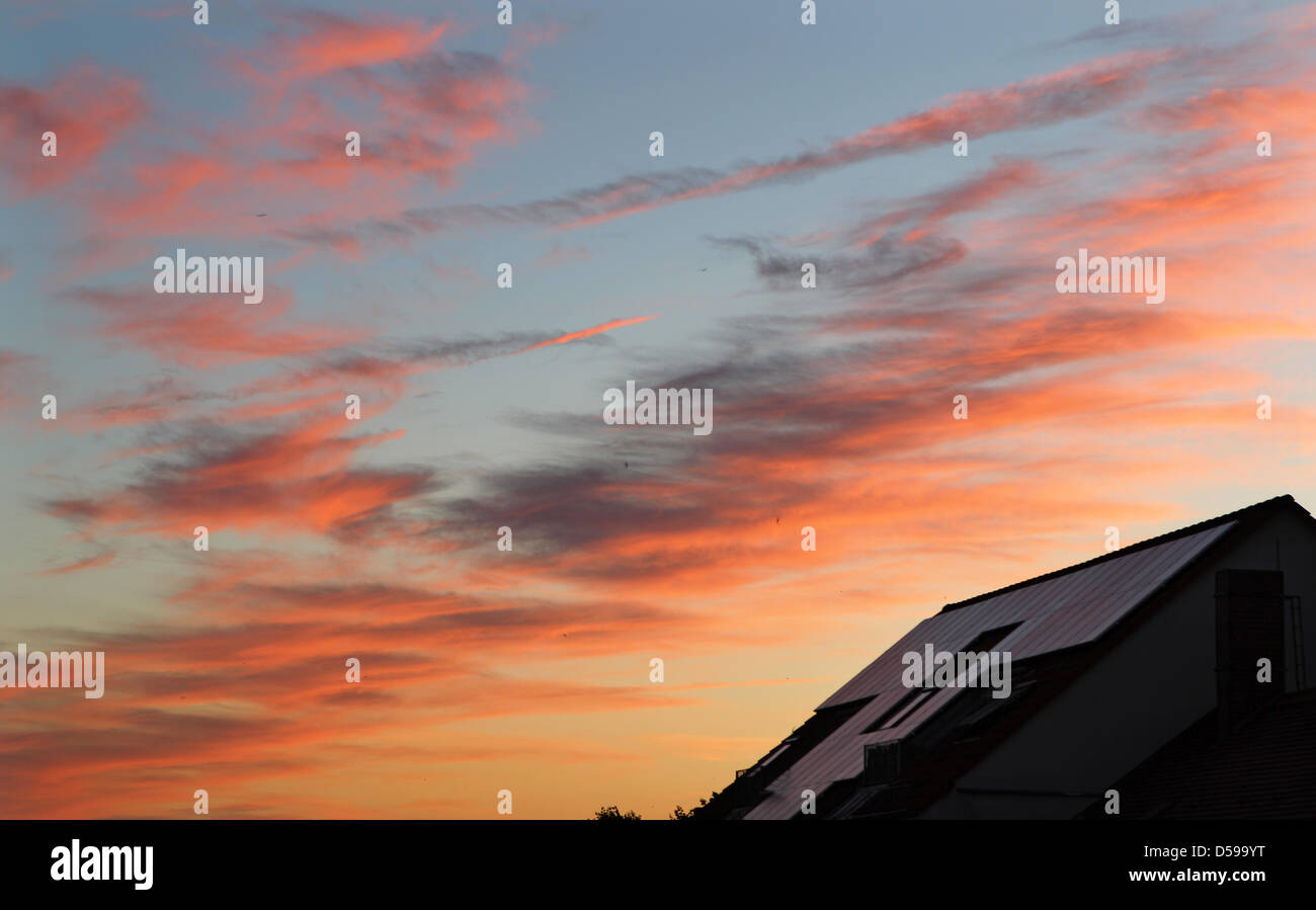 The clouds glow red over a house with solar collectors on its roof in Leipzig, Germany, 17 June 2010. A weather Stock Photo