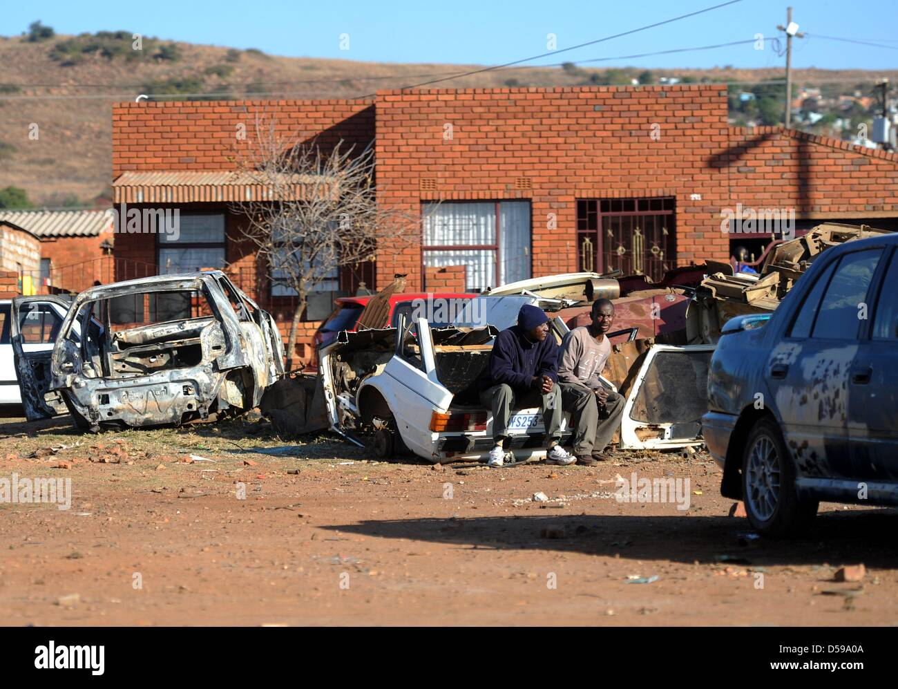 Local people sit on a scrapyard at the Atteridgeville township near Pretoria, South Africa, 16 June 2010. South - Stock Image