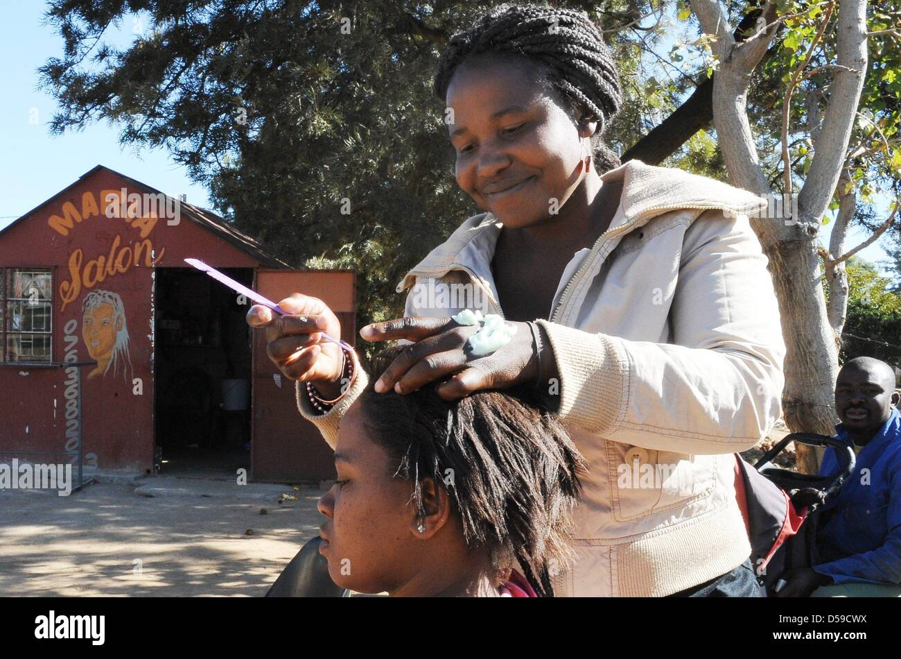 A young woman gets her done at Maria's Open Air Salon at a street close to Rustenburg's Royal Bafokeng Stadium - Stock Image