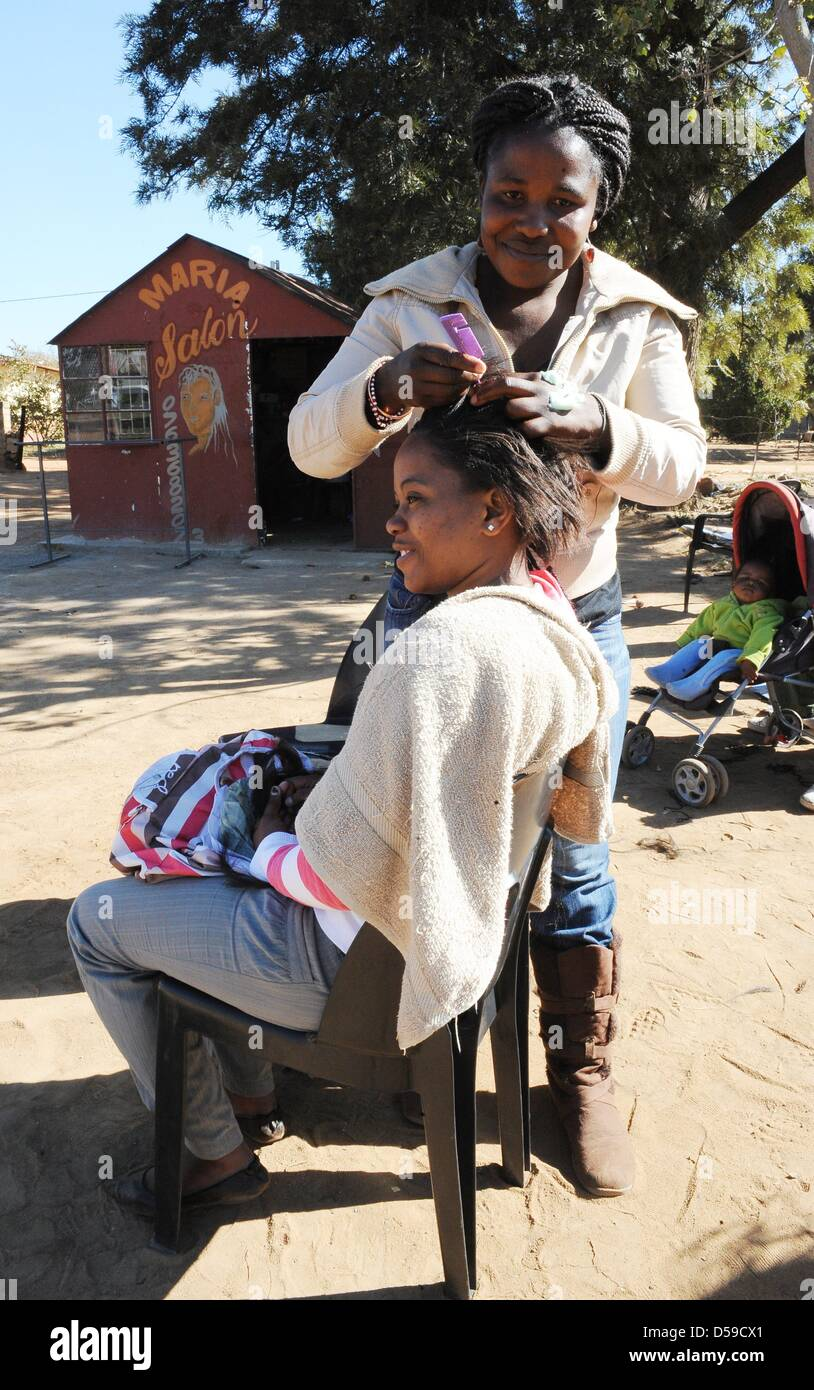 A young woman gets her hair done at Maria's Open Air Salon at a street close to Rustenburg's Royal Bafokeng - Stock Image