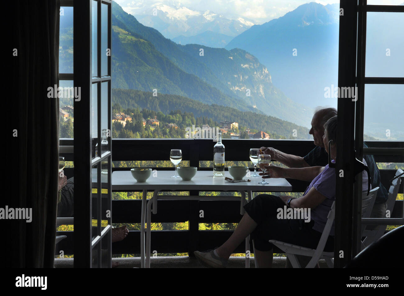 A retired couple enjoy a glass of wine on their Swiss Chalet balcony, Switzerland. - Stock Image