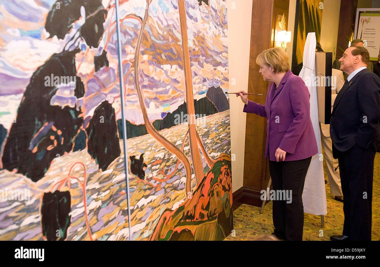 Bundeskanzlerin Angela Merkel malt neben Italiens Premierminister Silvio Berlusconi (r) während des G8-Gipfels - Stock Image
