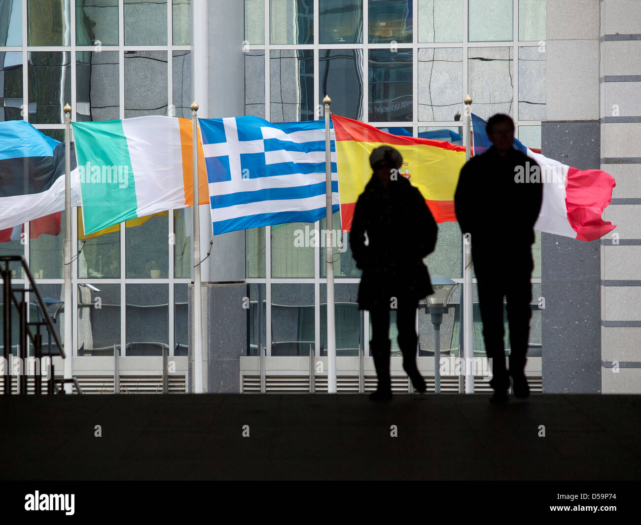 Waving flags of problem countries in front of the European Parliament building in Brussels, Belgium - Stock Image