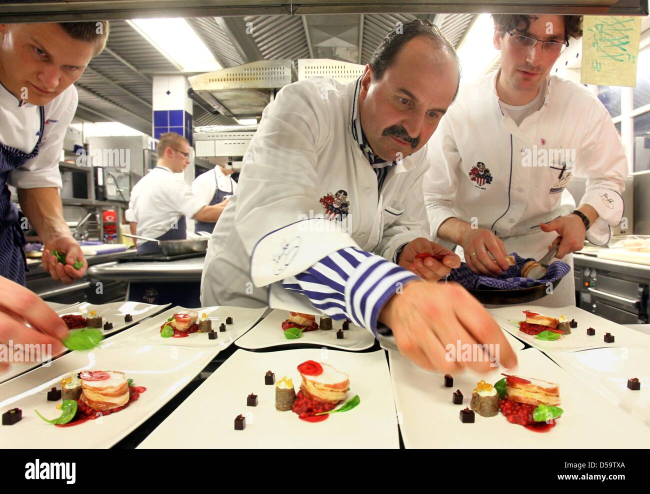 The gourmet chef Johann Lafer (M) arranges starter dishes in his ...