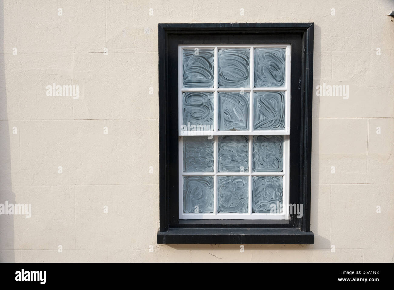 An old sash window with whitewash on the panes - Stock Image