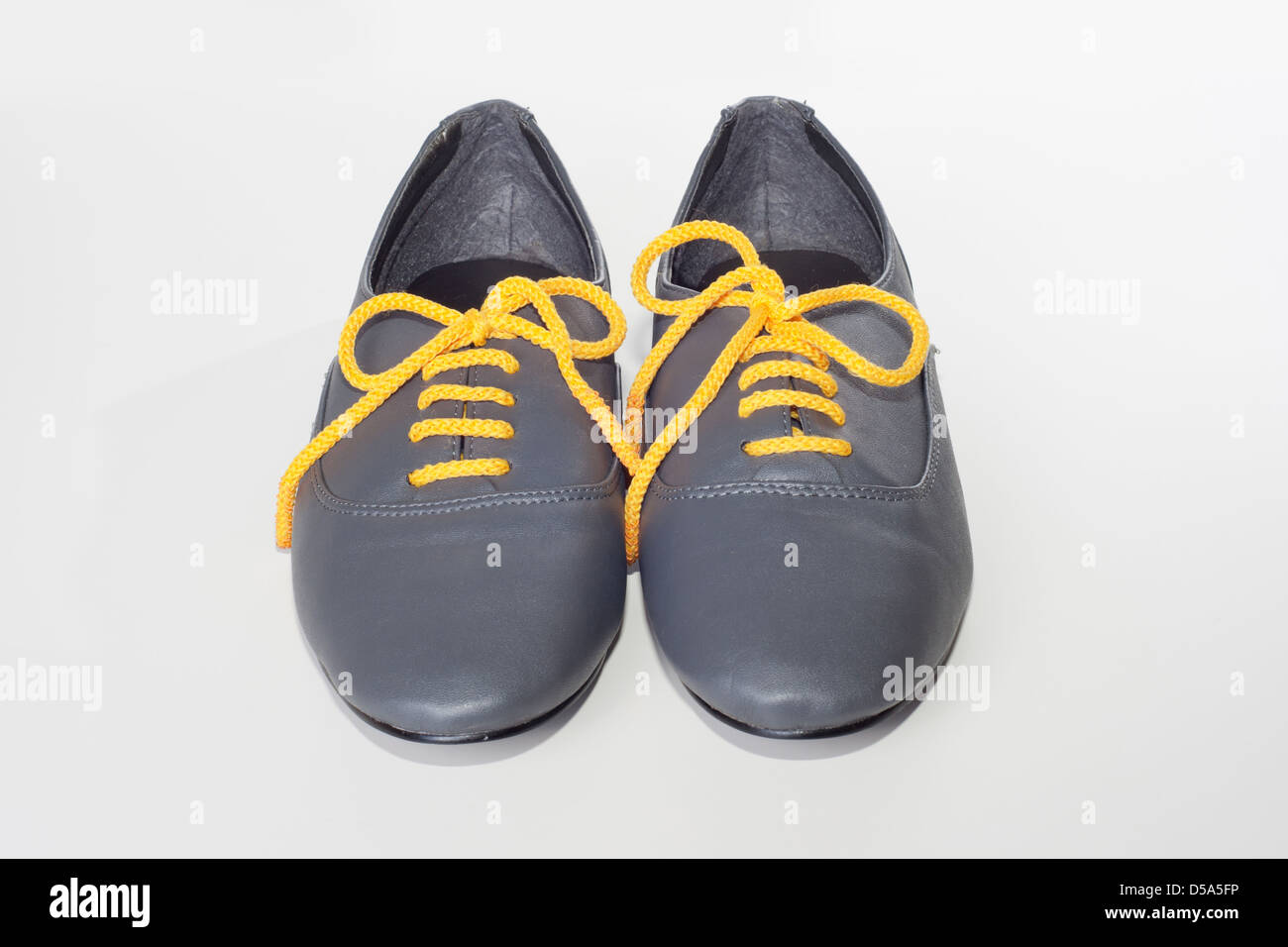 gray boots with yellow laces on a white background - Stock Image