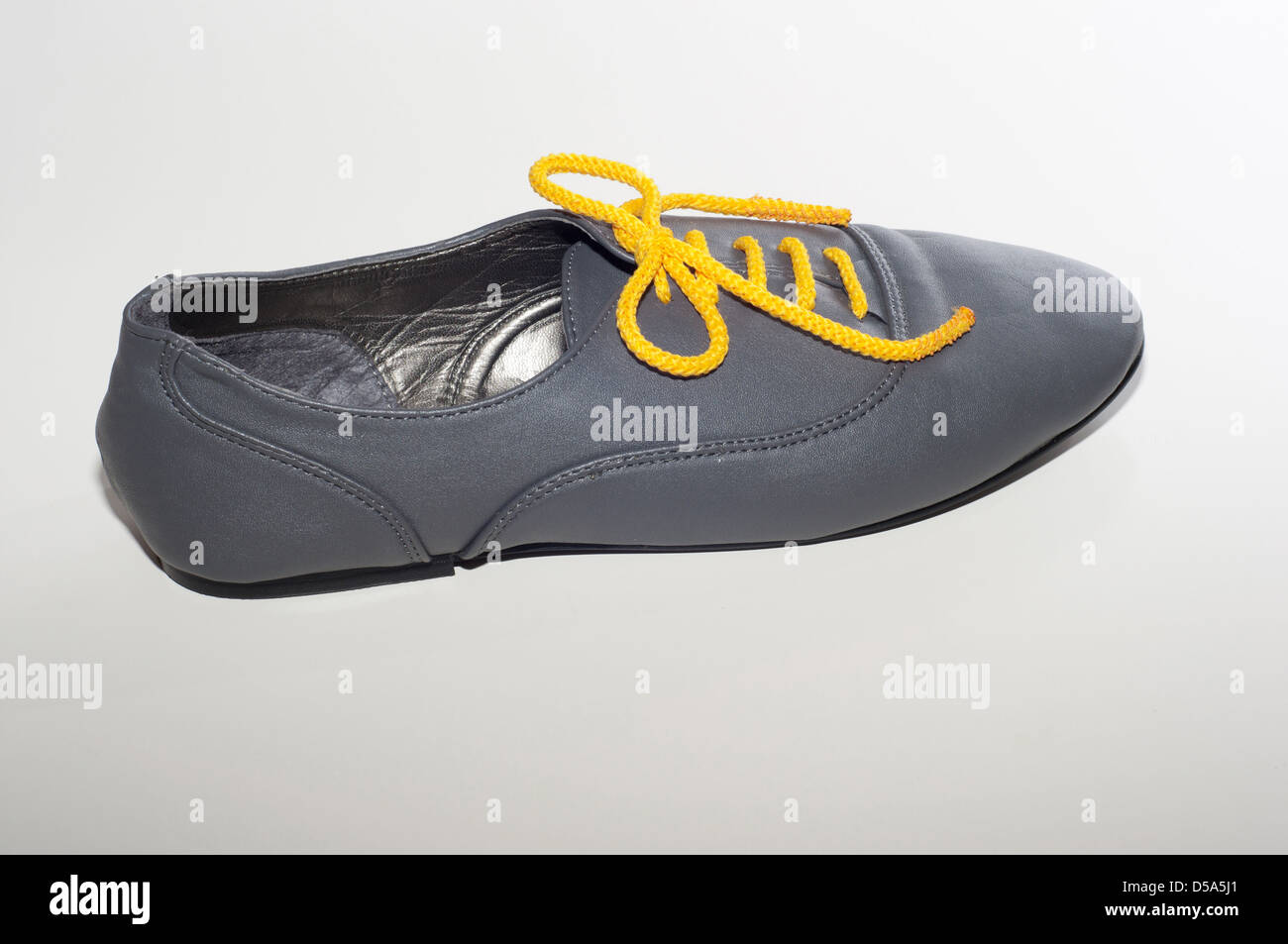 gray boot with yellow laces on a white background - Stock Image