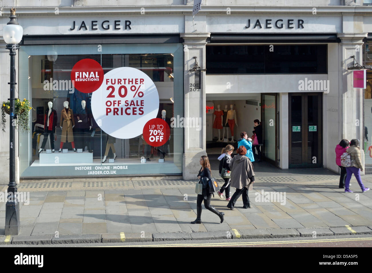 Regent Street fashion store Jaeger shop front window with sale discount posters - Stock Image