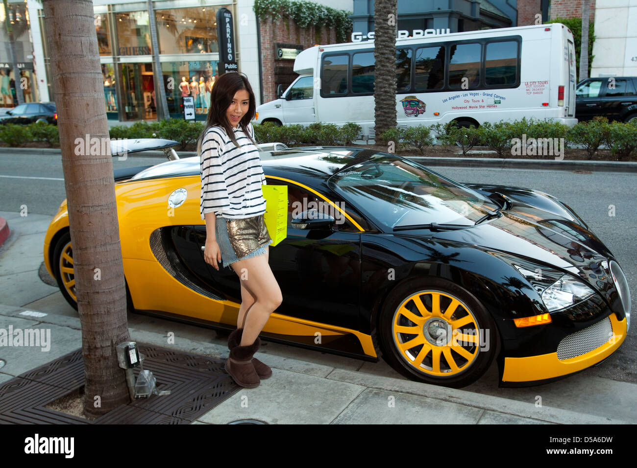 Girl posing with a Bugatti. Beverly Hills, Los Angeles County, California, United States - Stock Image