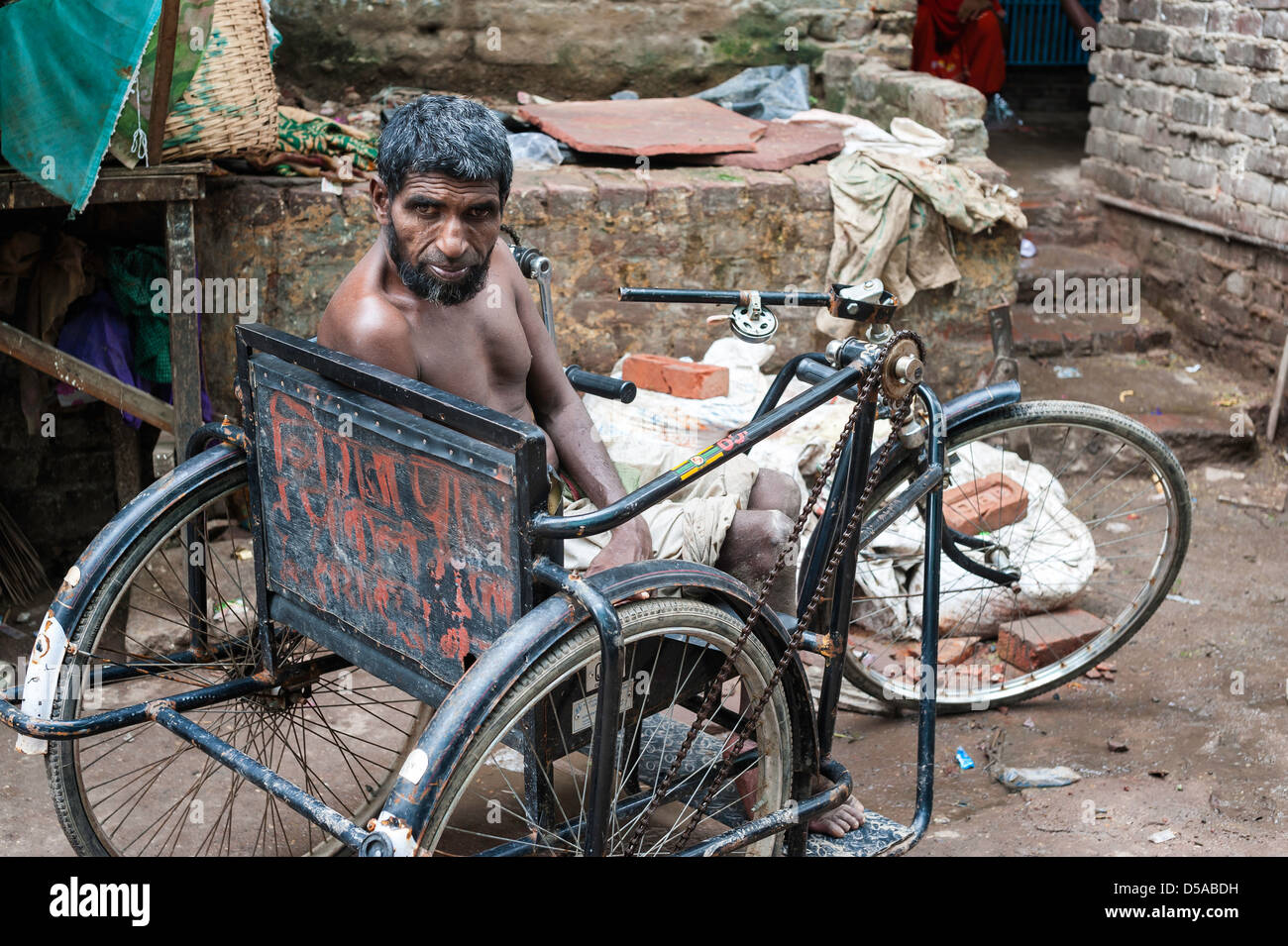 Man with disability in adapted tricycle begging in Nizamuddin, an old part of Delhi, India. - Stock Image