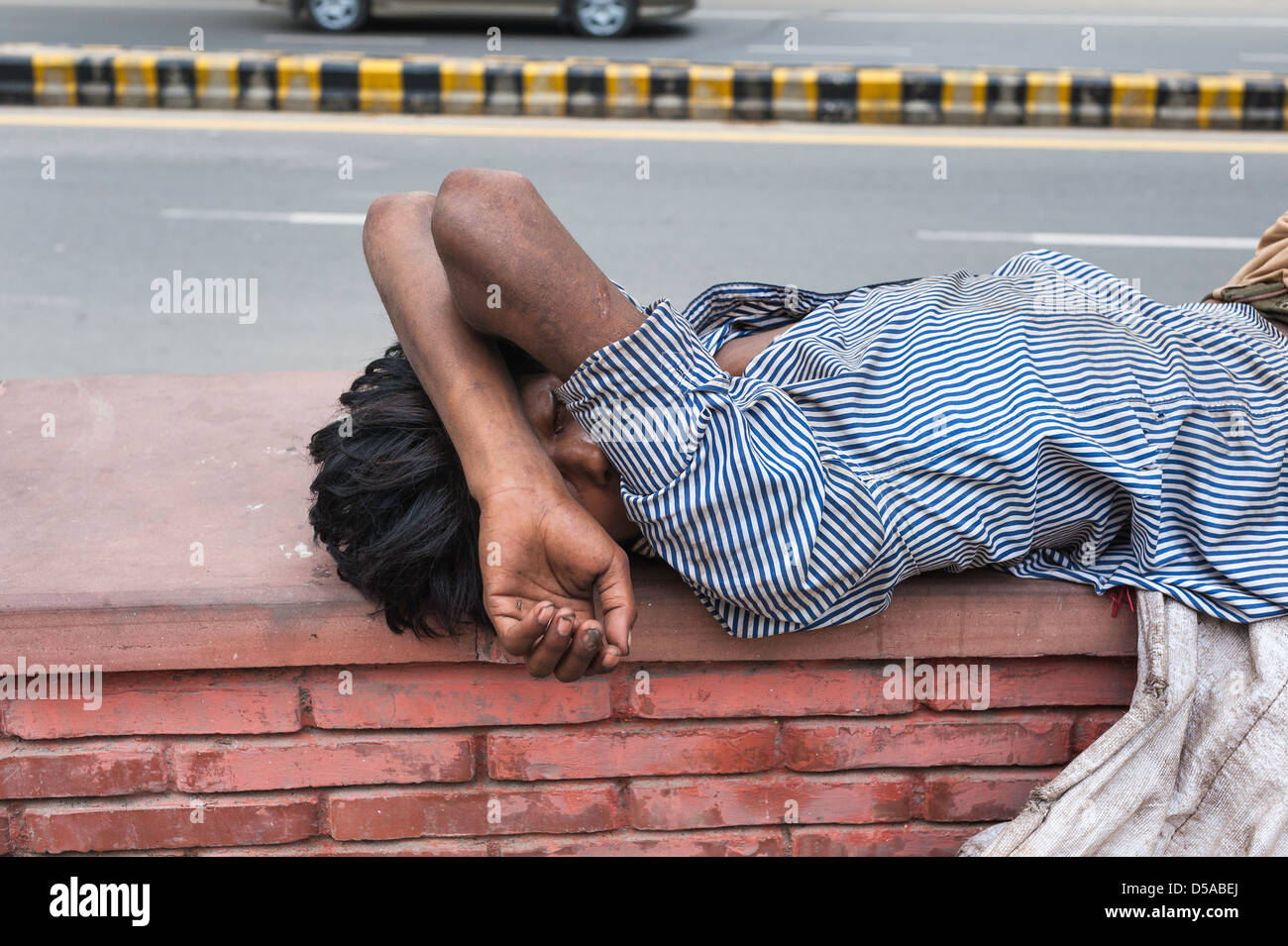 Homeless man asleep on side of busy road in Karol Bagh, a salubrious part of New Delhi, India. - Stock Image