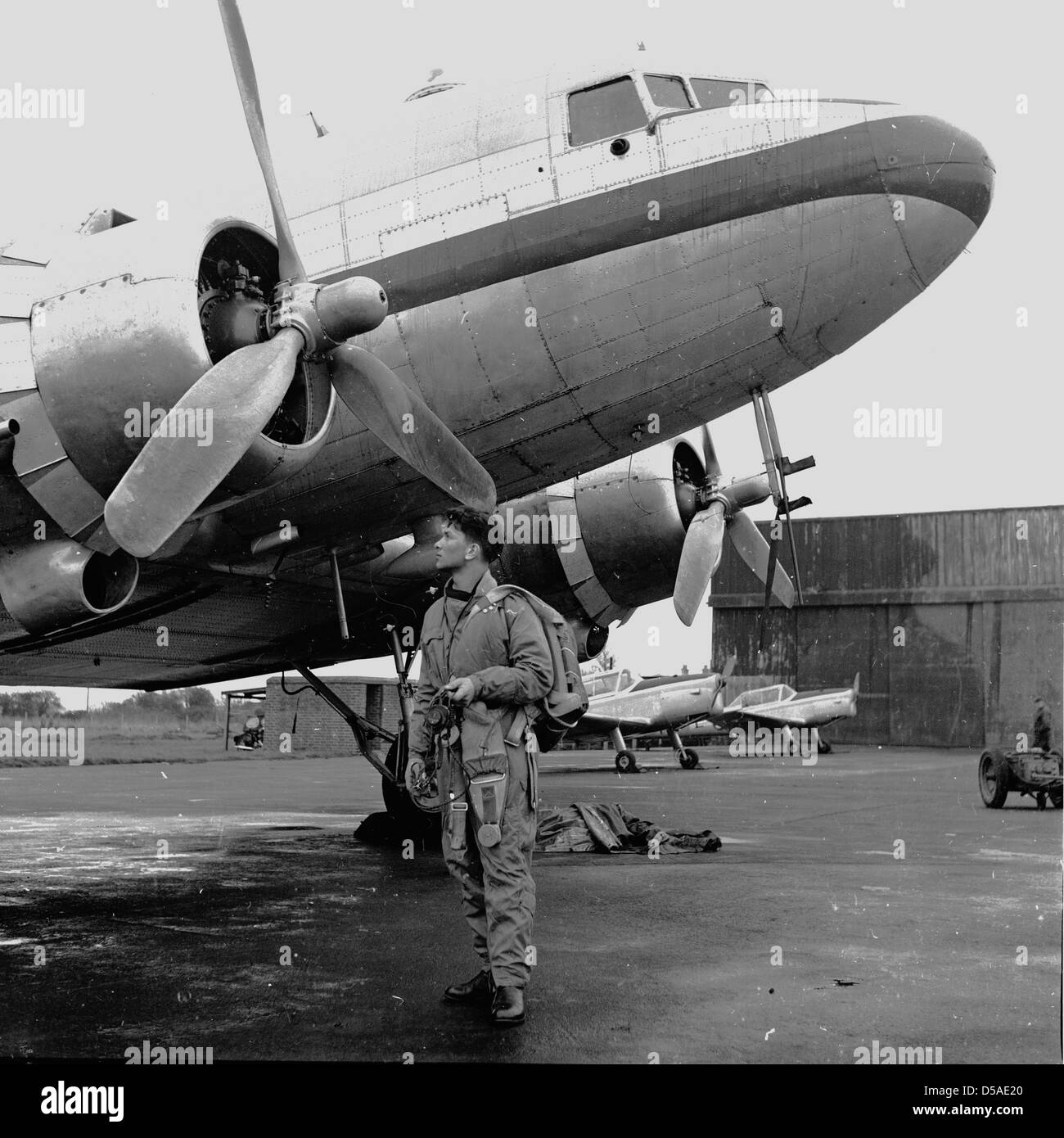 Historical 1950s. Flying. Young student pilot in flying clothing looks up a stationary aircraft on the runaway. Stock Photo