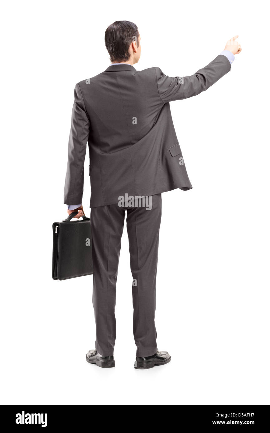 Full length portrait of a businessman pointing in a direction, shot from behind, isolated on white background - Stock Image