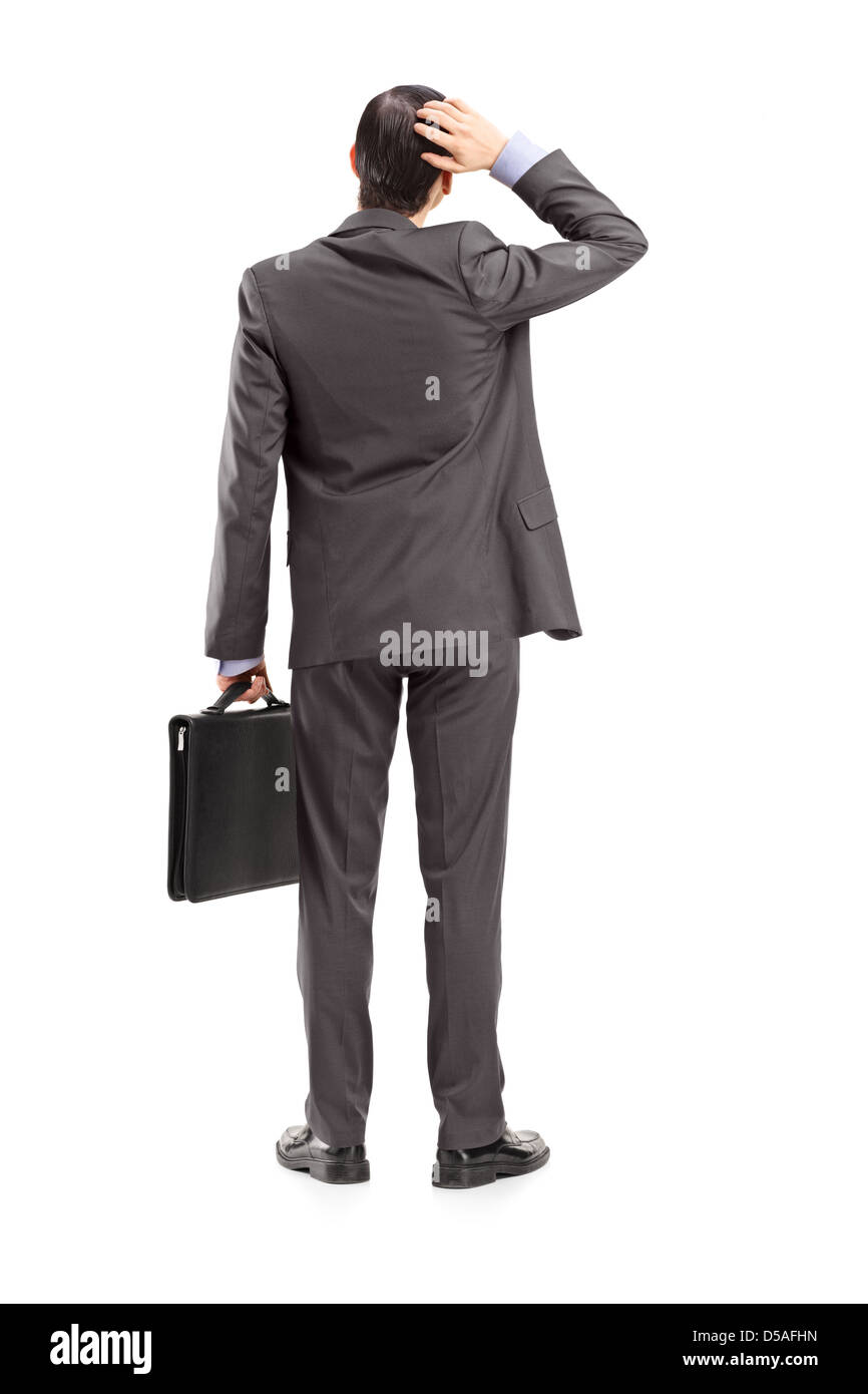 Full length portrait of a businessman with briefcase, holding his head, shot from behind, isolated on white background - Stock Image