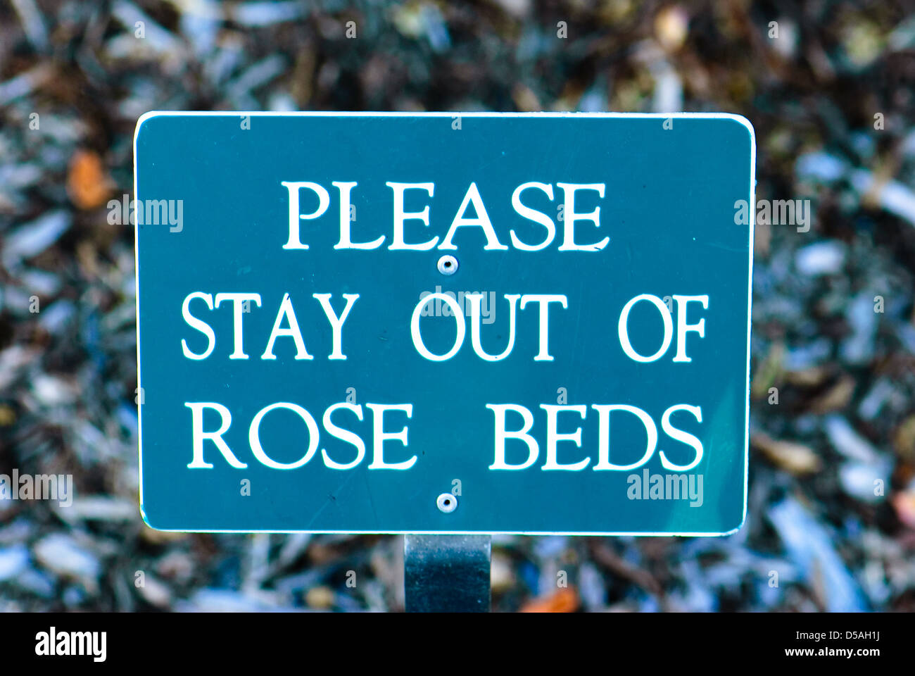 Sign that says Please stay out of rose beds. - Stock Image