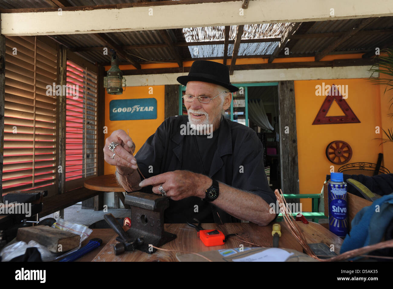 An older man working at jewellery making. - Stock Image