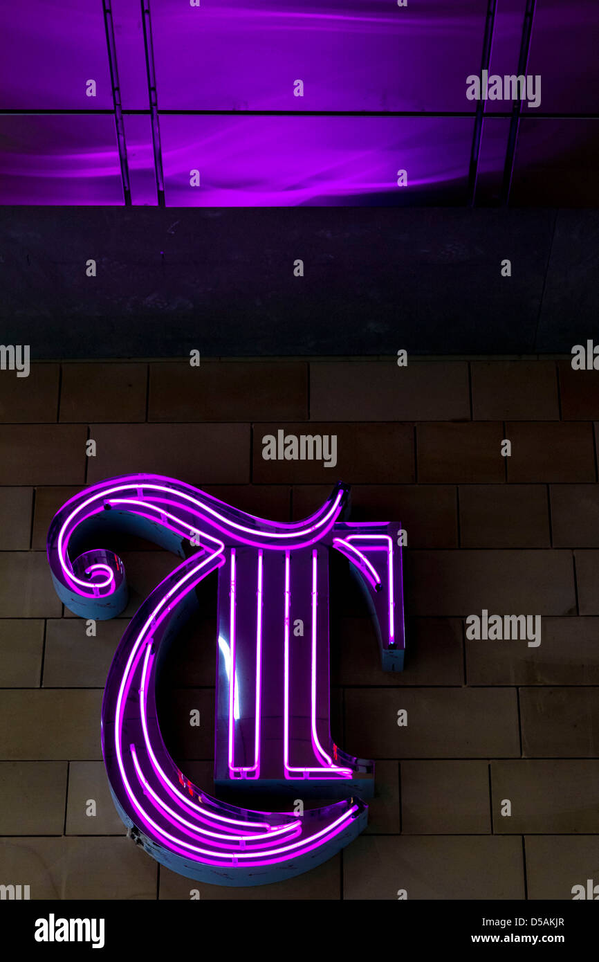 A purple letter T from the Trinity shopping centre in Leeds with purple light above it. - Stock Image