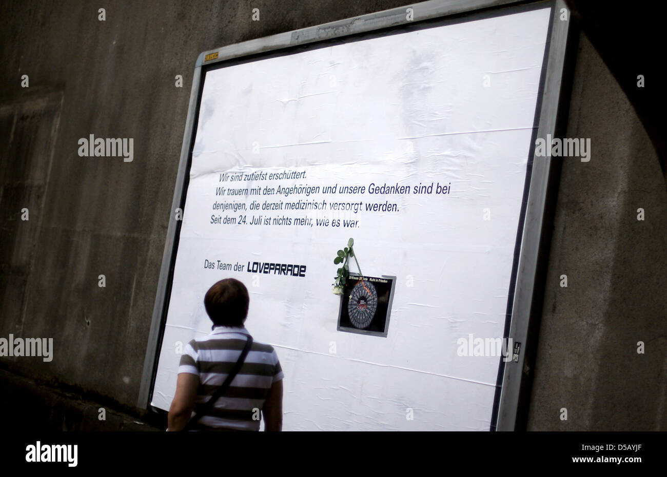 A man takes a photo of a poster expressing the Love Parade's organisers' dismay in Duisburg, Germany, 27 - Stock Image
