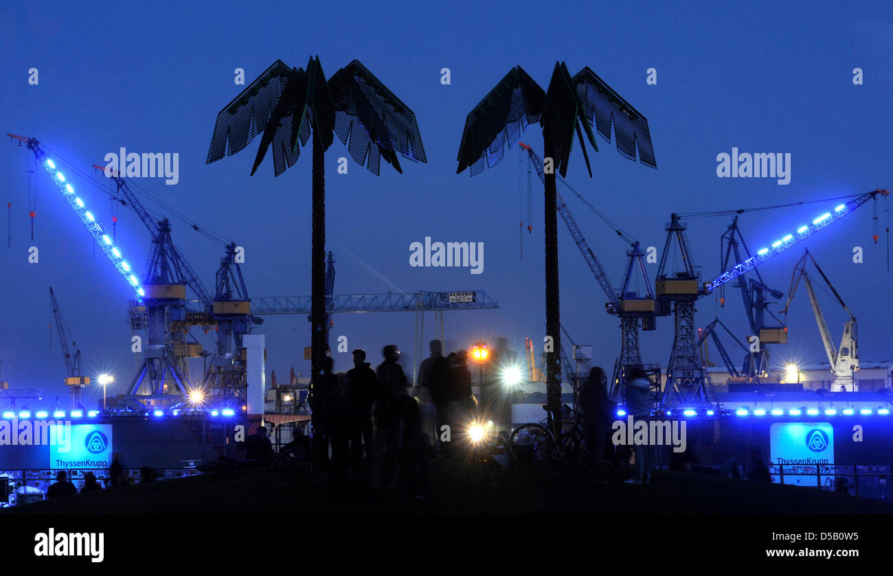 People look at the wharf Blohm and Voss, which is illuminated in blue light, in Hamburg, Germany, 30 July 2010. - Stock Image