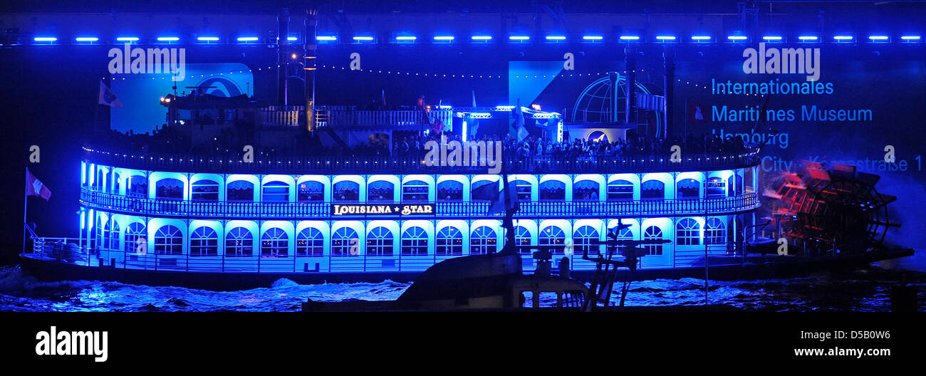 The paddle wheel steamer 'Luisiana Star' passes the wharf Blohm and Voss, which is illuminated in blue light, - Stock Image