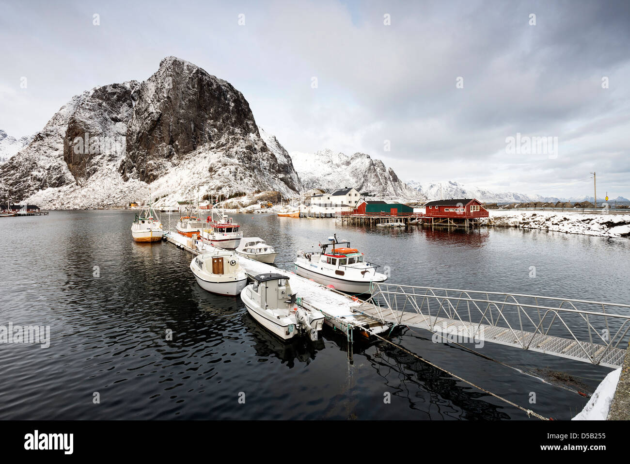 A view of boats tied up in the pretty harbour at Hamnoy, with Lilandstinden in the background - Stock Image