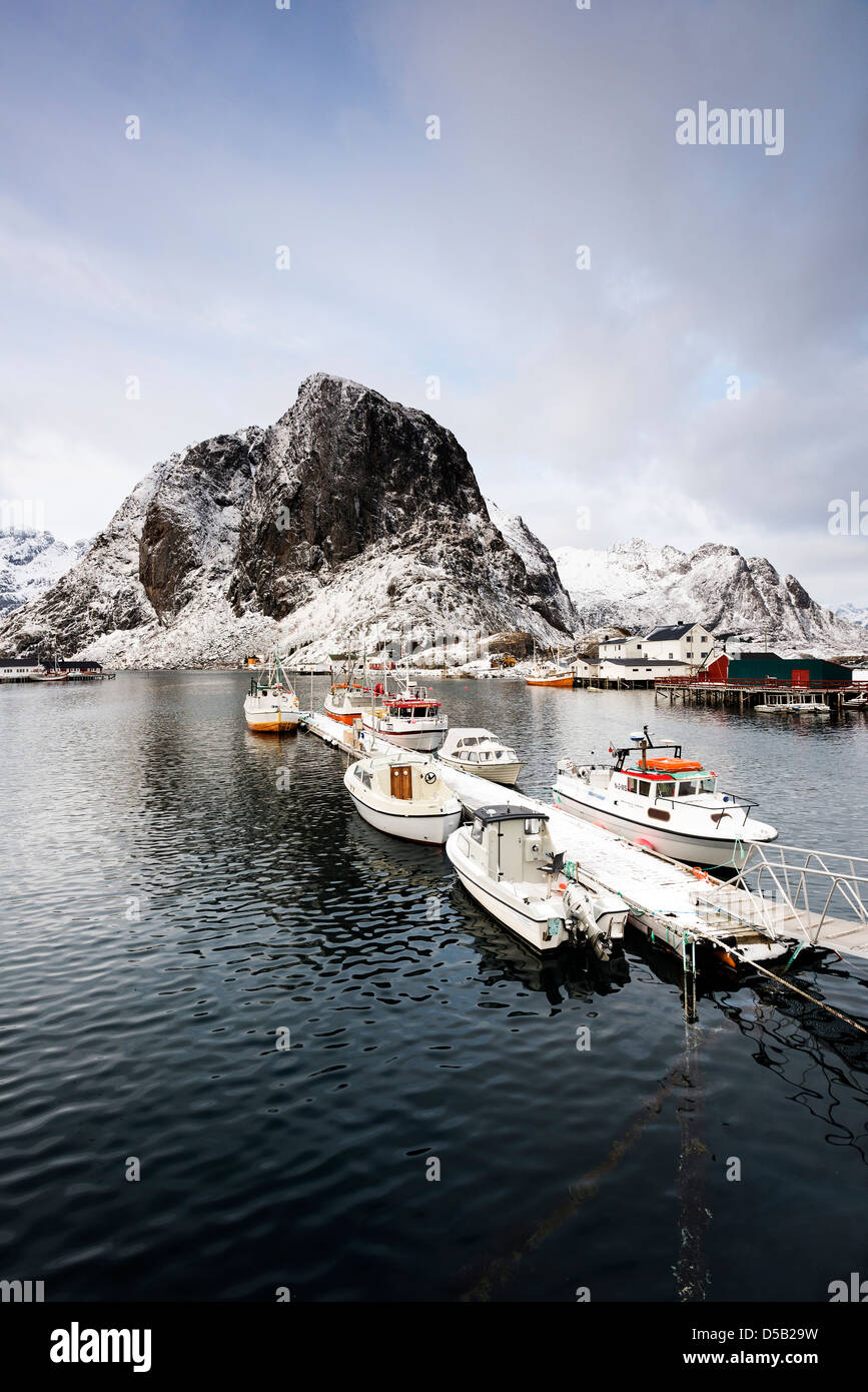 A view of boats tied up in the pretty fishing harbour at Hamnoy, with Lilandstinden in the background - Stock Image