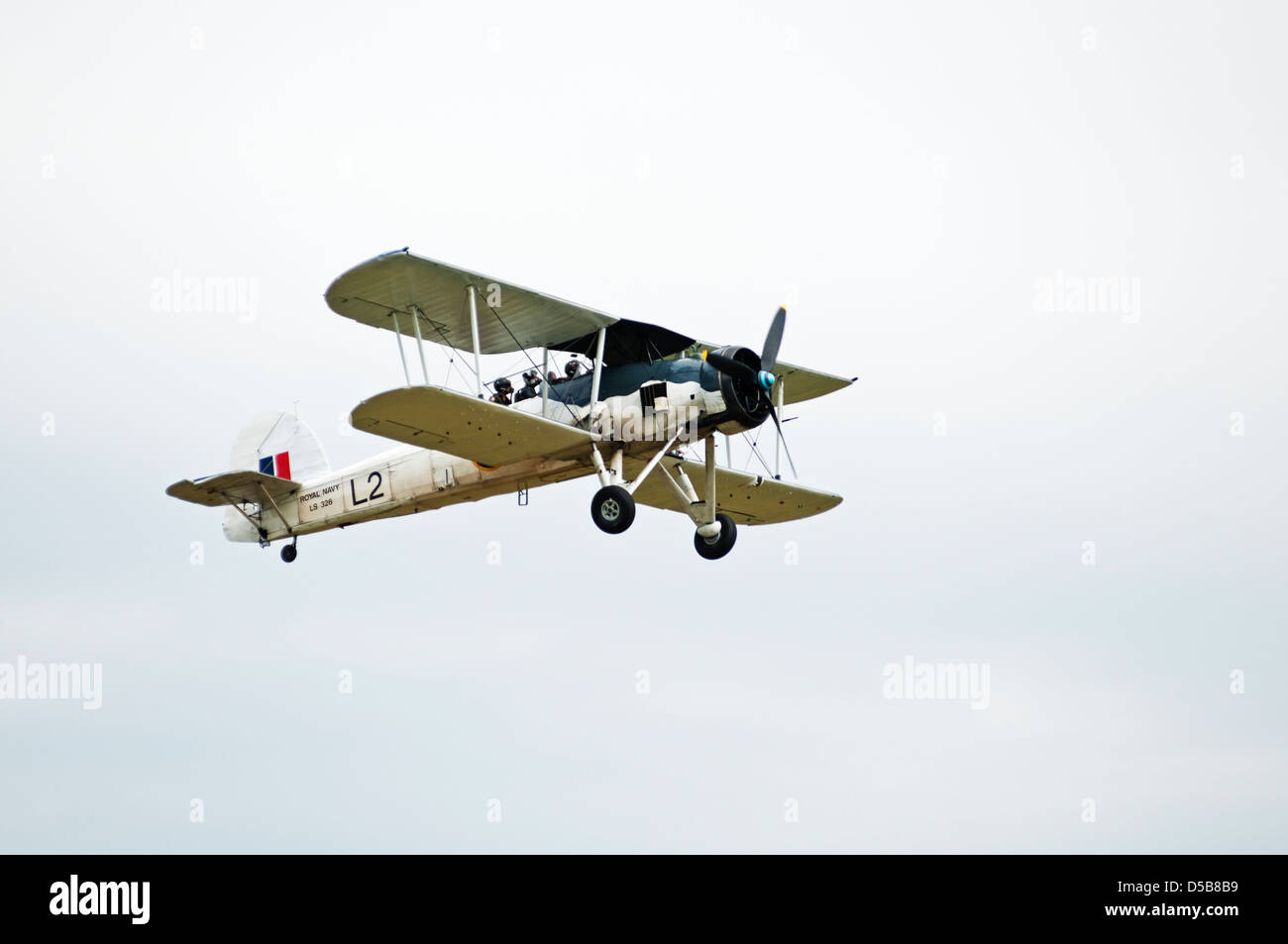 Seen from the ground, a vintage Swordfish bi-plane of the Royal Navy performs a fly-past at an air show. - Stock Image