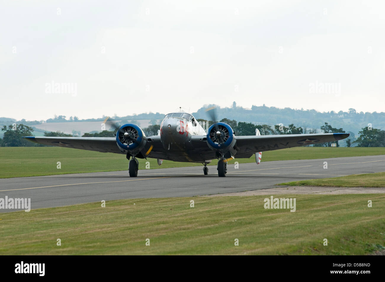 A vintage twin engined Beech 18 aircraft taxying along an airfield runway. - Stock Image
