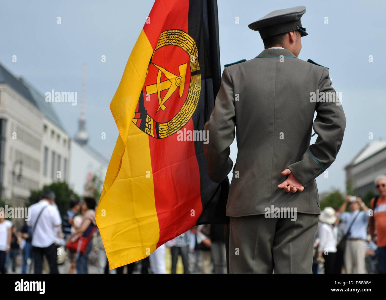 A man clad in an East German army uniform poses with a GDR