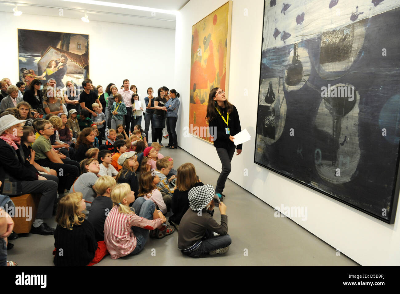 During a tour by children for children, 13 year-old Lisa interprets the paintings 'Dromos' (R) and 'Erl'(C) - Stock Image