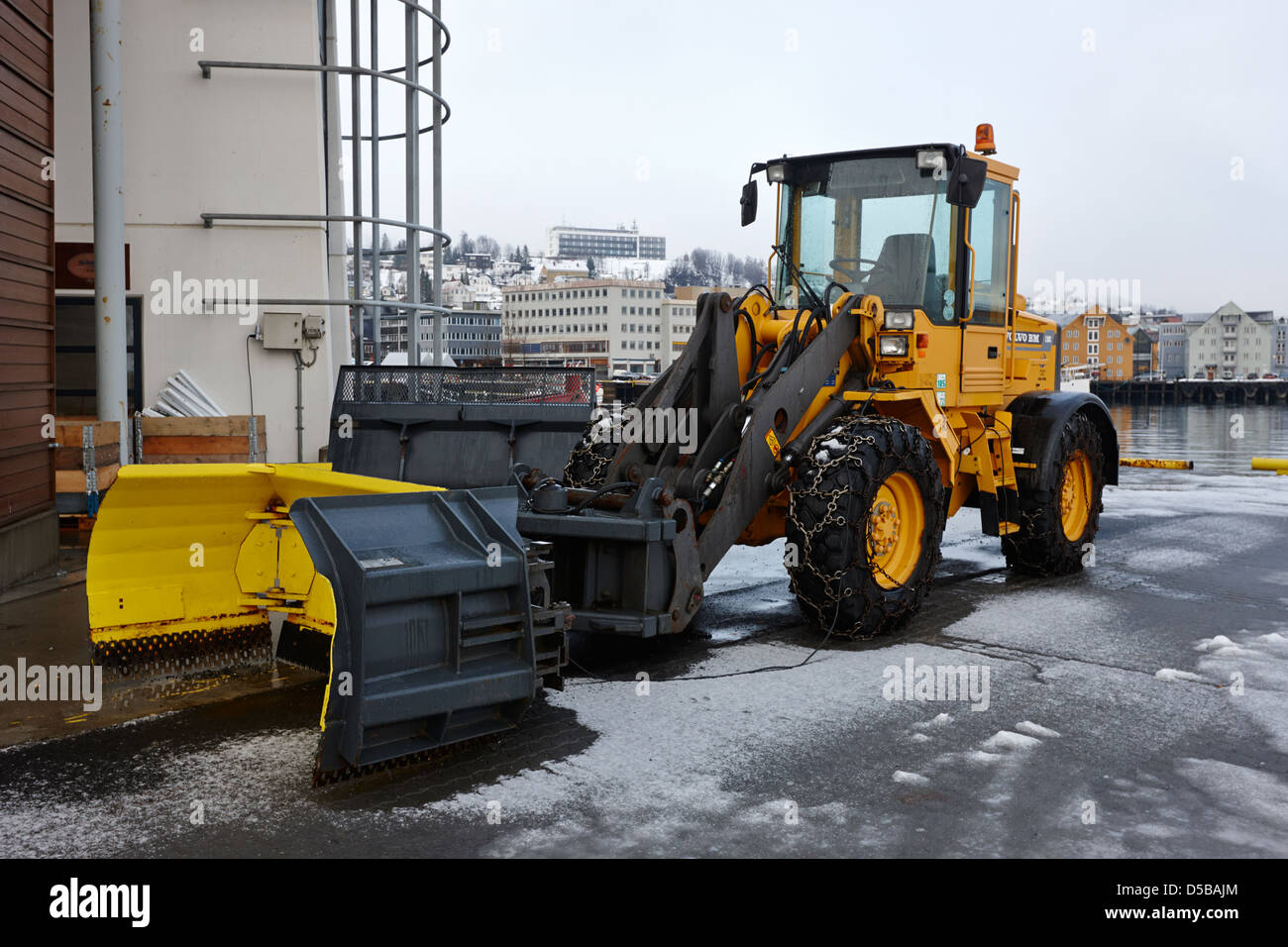 heavy duty volvo plant with snow clearing attachment Tromso harbour troms Norway europe - Stock Image