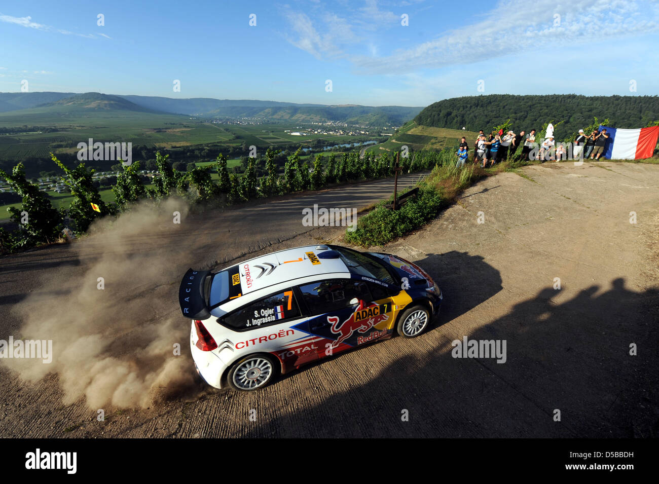 French Sebasien Ogier and co-driver Julien Ingrassia drift in their Citroen C4 WRC in the Mosel vineyards during - Stock Image
