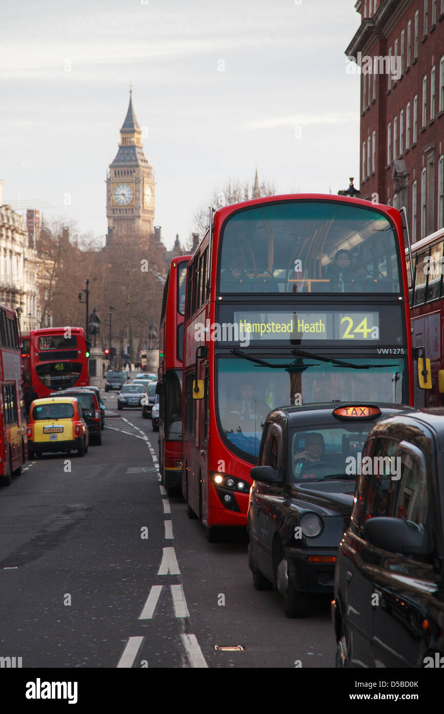 London Buses and Taxis in Whitehall, London with Big Ben in the distance showing the time 1745 GMT. - Stock Image
