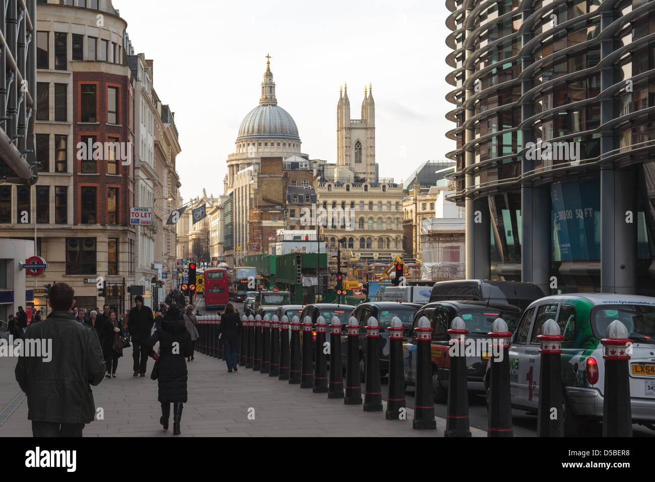Taxis, traffic and people on Cannon Street, London with St. Paul's Cathedral visible in the distance - Stock Image