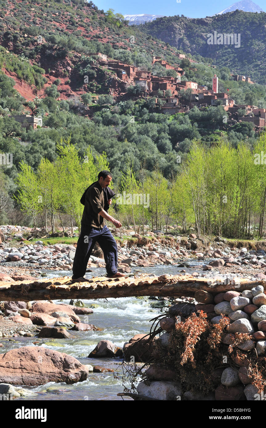Man crosses a bridge over the  river Oued Ourika that cascades down the Ourika Valley from the High Atlas Mountains - Stock Image
